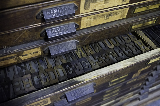 Brooklyn, USA - 24 February 2018: Close up of wooden printing blocks in a tray in a display cabinet in a printing shop
