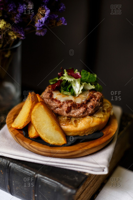 Gourmet open-faced hamburger served with potato wedge fries