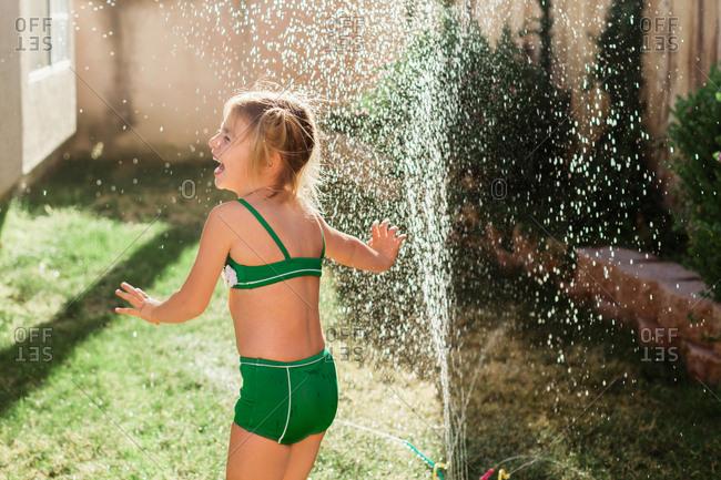 Little girl having fun cooling off in the sprinkler
