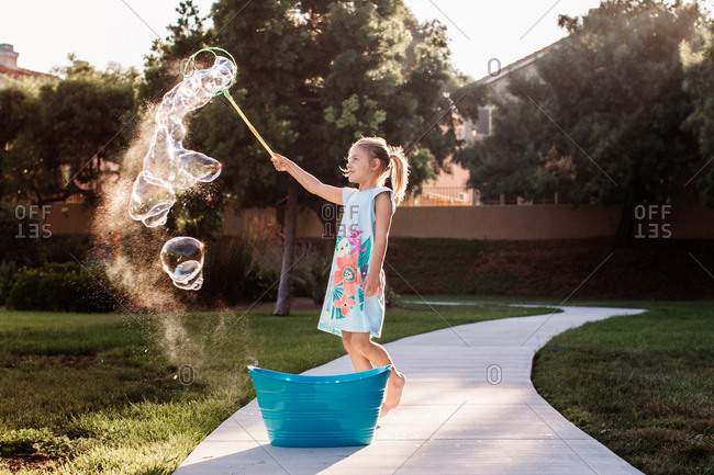 Young girl making large bubbles with wand outside on a sunny day