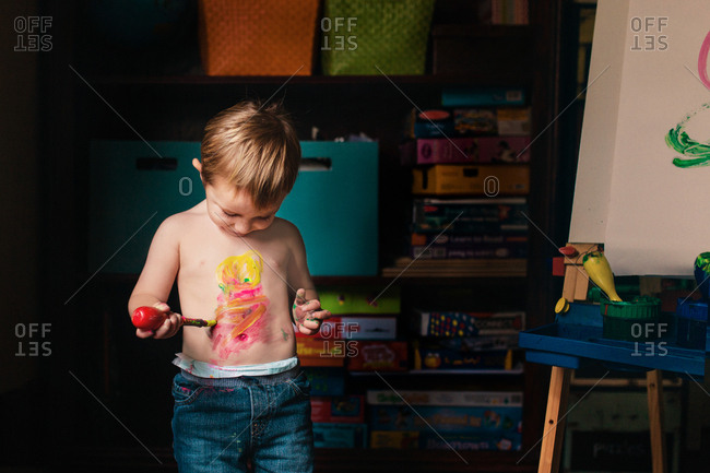 Creative toddler painting his chest in art room