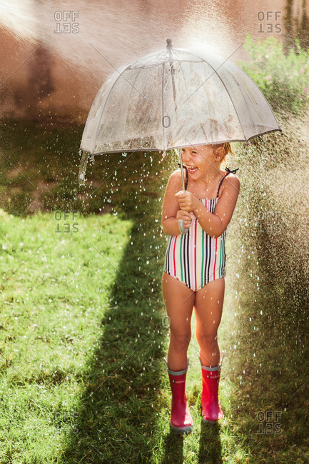 Happy little girl playing with umbrella under sprinkler outside