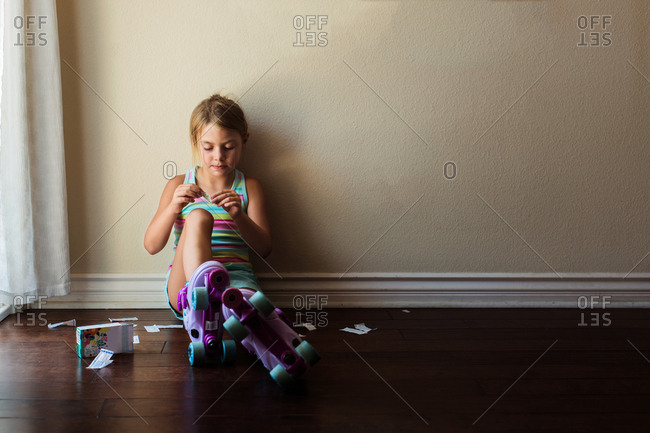 Young girl putting on bandages for roller skating injury