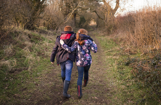 A brother and sister walking with their arms around each other on a country walk.