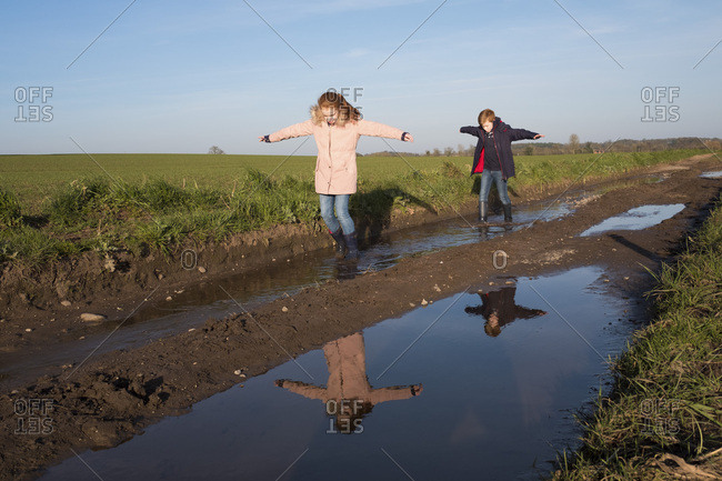 A teenage boy and girl splashing in puddles of mud on a country walk