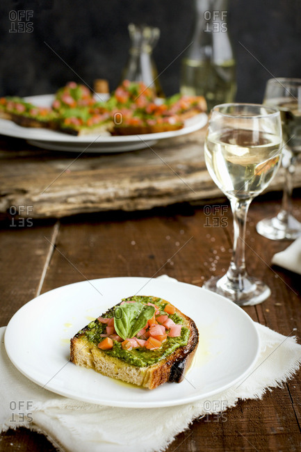 Kale asiago pesto crostini with quick pickled vegetables and basil served with white wine