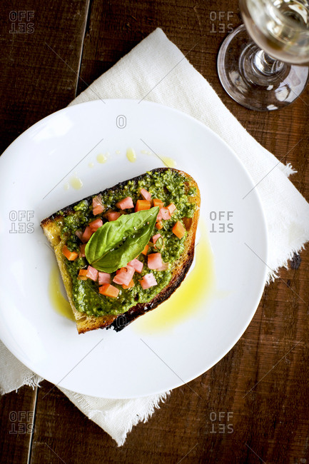 Kale asiago pesto crostini with quick pickled vegetables and basil