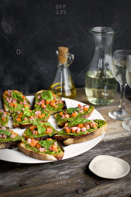 Plate of kale asiago pesto crostini served with white wine and olive oil