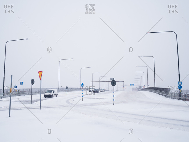 Cars travelling down a snowy road towards a crossroads in Malmo, Sweden