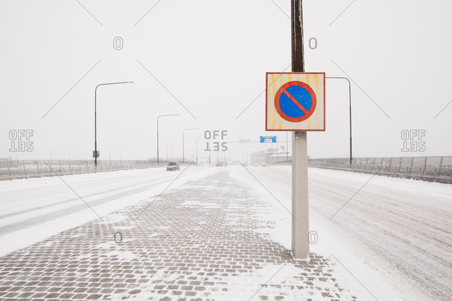 Cars driving along snowy highway with street sign in foreground in Malmo, Sweden