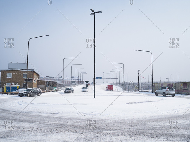 Cars driving around a snowy traffic circle in Malmo, Sweden