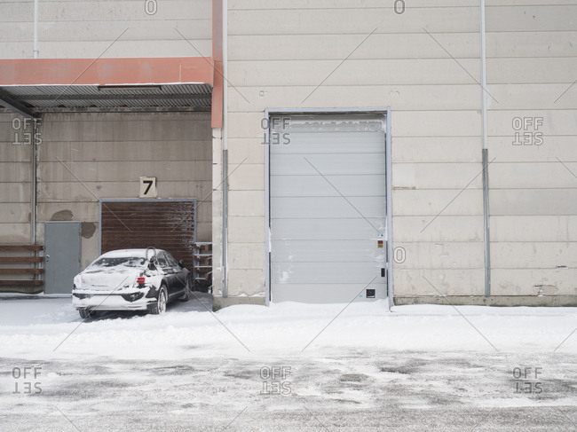 Car covered in snow outside warehouse in Malmo, Sweden