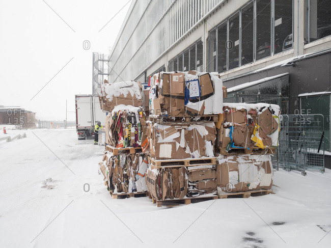 Malmo, Sweden - 28 February, 2018: Palettes of waste cardboard prepared for transportation in the falling snow