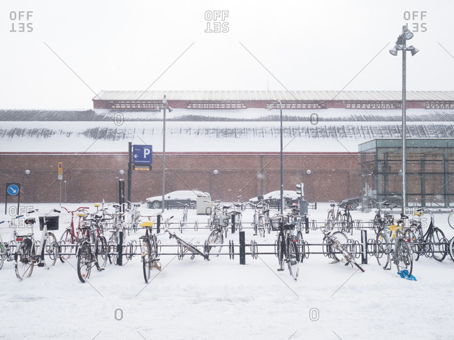 Bicycles left in bicycle racks in the falling snow in Malmo, Sweden