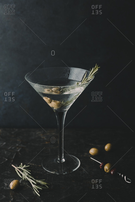 Dry martini with olives and rosemary garnish