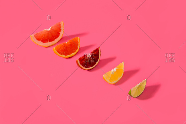 Wedges of seasonal fruit on a pink background