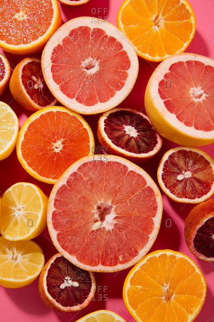 Fresh slices of citrus on a bright pink background