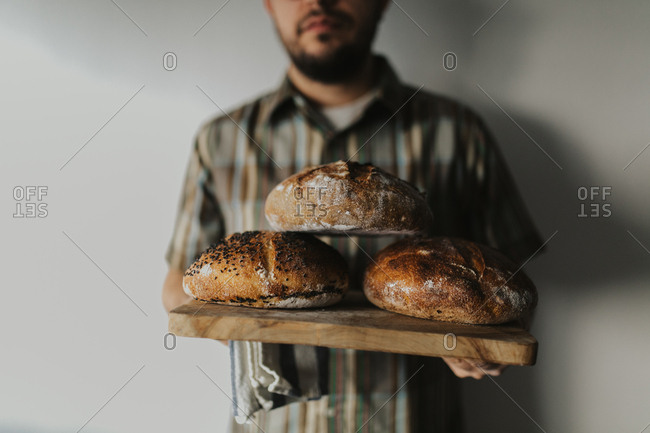 Man holds freshly baked loaves of sourdough bread