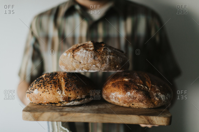 Detail of a man holding freshly baked loaves of sourdough bread on a wooden cutting board