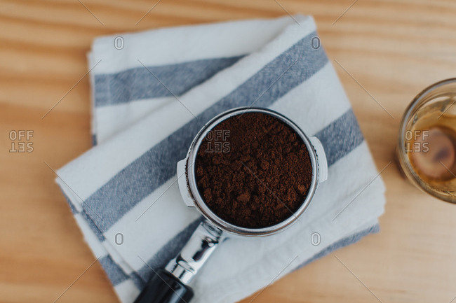 Espresso portafilter filled with ground coffee for an espresso shot