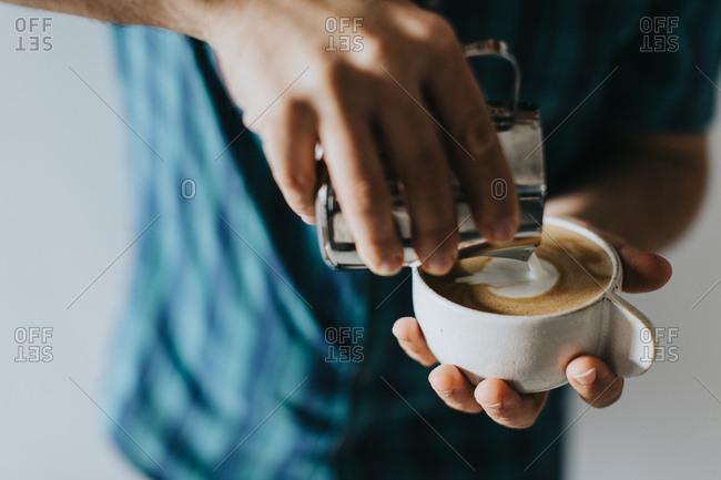 Barista pouring steamed milk into espresso to make a cappuccino