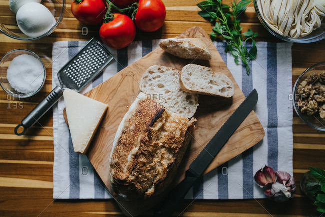 Loaf of bread and fresh ingredients to cook a fresh Italian meal