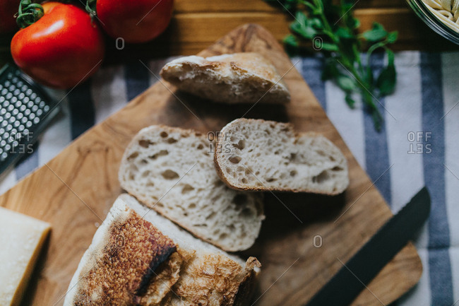 Sliced loaf of bread and fresh ingredients to cook a fresh Italian meal
