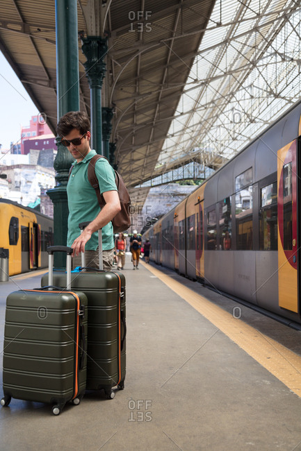 Porto, Portugal - July 27, 2017: Tourist readies his luggage on the train station platform