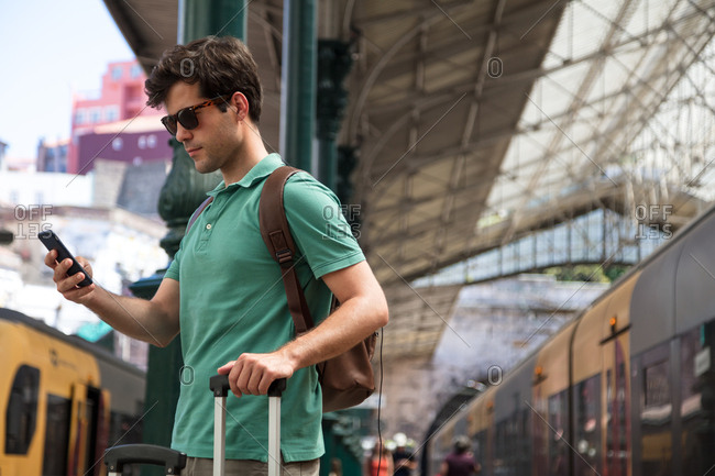Backpacker studies his mobile at on the train station platform
