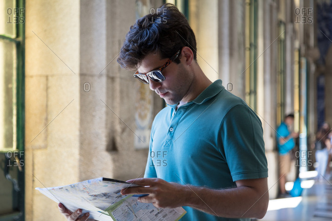 Porto, Portugal - July 27, 2017: Tourist studies a map on vacation