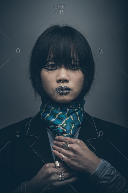 Moody low key fashion portrait of model with septum piercing adjusting tie