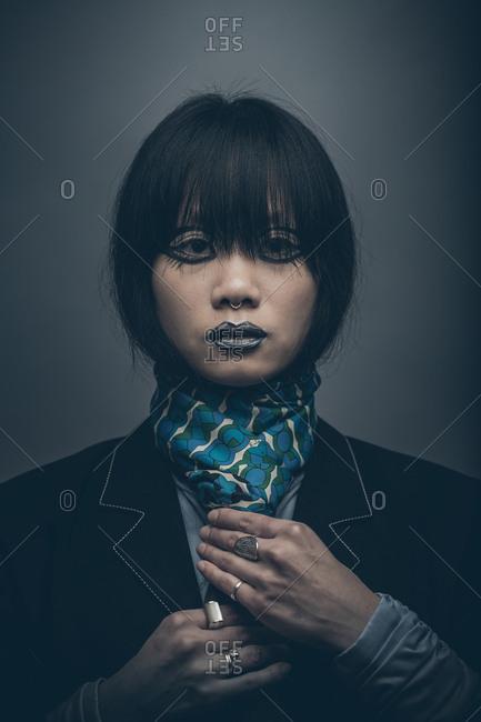 Moody low key fashion portrait of model with septum piercing adjusting tie
