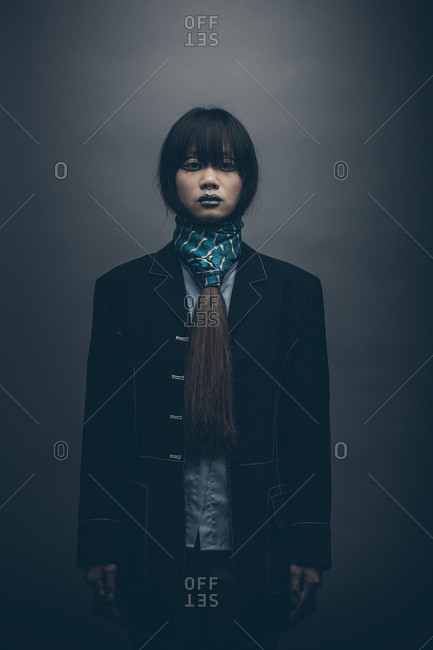 Moody low key fashion portrait of model standing with hands by side