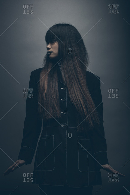 Moody fashion portrait of model standing with hands raised by side looking off camera