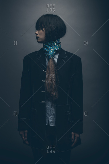 Moody low key fashion portrait of model standing with hands by side looking off camera