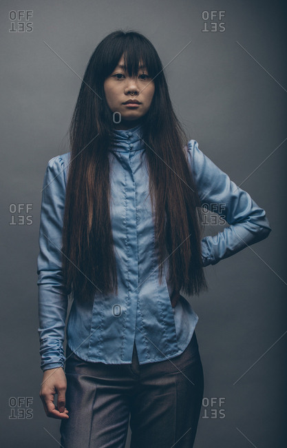 Model posing with long hair over shoulders and hand on hip