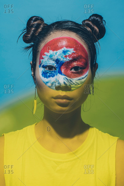 Yellow hued portrait of model with wave painted on face