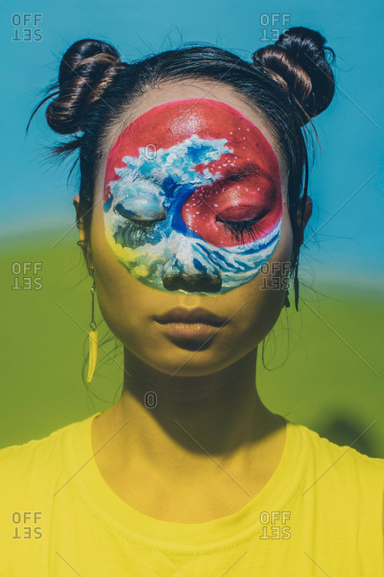 Yellow hued portrait of model with eyes closed and wave painted on face