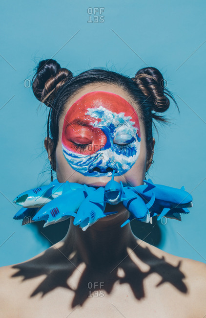 Portrait of model with wave painted on face and holding toy sharks in mouth with eyes closed