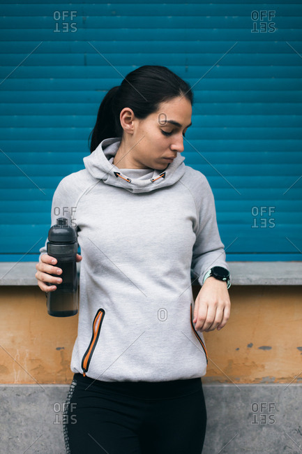 Sporty young woman taking a break for drinking water while checking the workout rest time