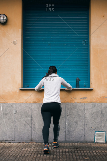 Back view of female runner stretching calves for warming up before running and exercising