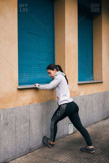 Female runner stretching calves for warming up before running and exercising