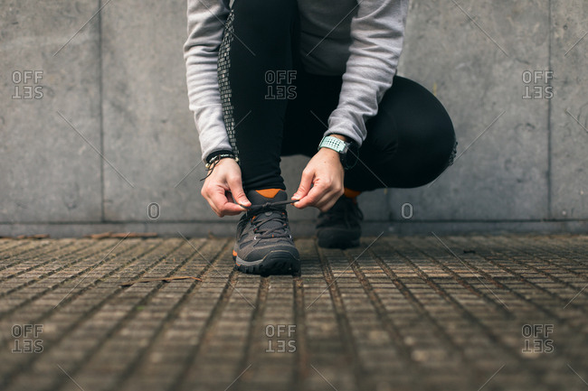 Close up of woman lacing running shoes before training