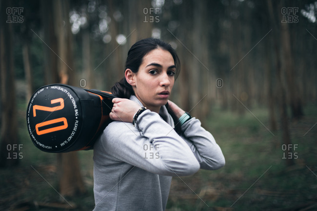 Sporty motivated fitness woman working out with heavy bag outdoors