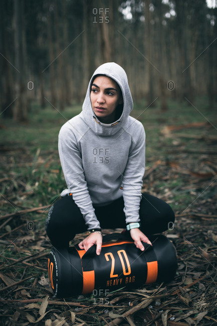 Fitness strong woman taking a break after training outdoors with heavy bag during hiit and strength workout