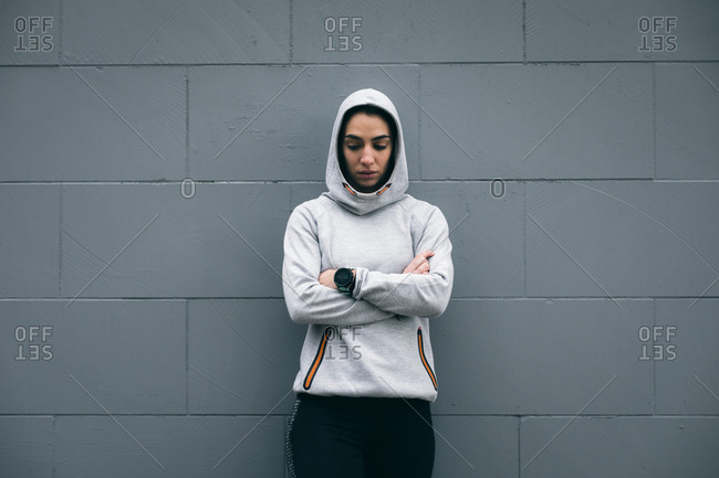 Sporty tough fitness woman taking a workout rest leaning on a wall