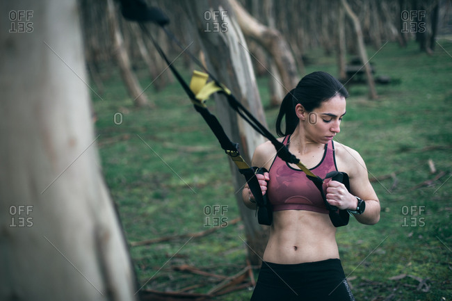 Strong young woman training back and arms with trx suspension fitness straps outdoor