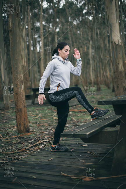 Sporty young woman doing toe taps during outdoor hiit workout