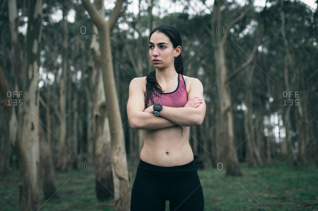 Empowered young fitness woman with arms crossed during outdoor workout
