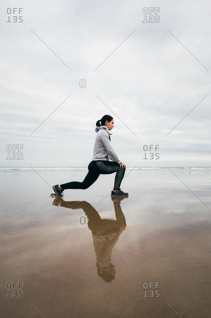 Sporty woman on fitness workout doing lunges at the beach in winter